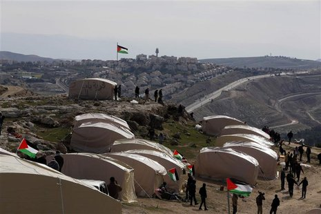 Palestinians, together with Israeli and foreign activists, stand near newly-erected tents in an area known as E1, near Jerusalem January 12,