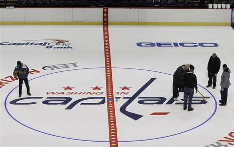 Workers put the finishing touches on the installation of the Washington Capitals logo at center ice during the laying down process of the pl