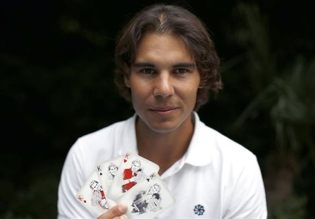 Spanish tennis player Rafa Nadal poses with playing cards depicting some of his 11 Grand Slam victories after an interview with Reuters in M