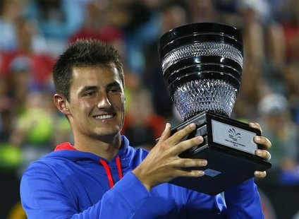 Bernard Tomic of Australia poses with the trophy after defeating Kevin Anderson of South Africa during their men's final match at the Sydney
