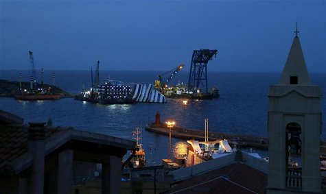 The capsized cruise liner Costa Concordia is pictured surrounded by cranes outside Giglio harbour January 12, 2013. REUTERS/Stefano Rellandi