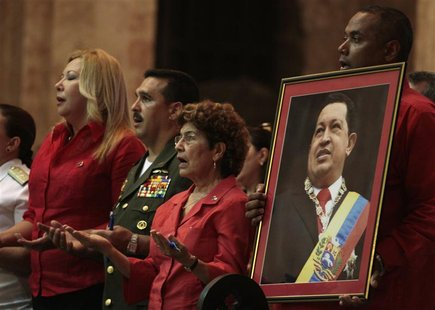 A Venezuelan man holds a picture of Venezuela's President Hugo Chavez during a mass to pray for his recovery at a church in Havana January 1