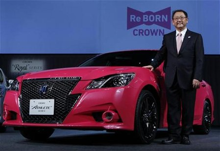 "Toyota Motor Corp President Akio Toyoda poses next to the company's remodeled ""Crown Athlete"" at an unveiling in Tokyo December 25, 2012. RE"