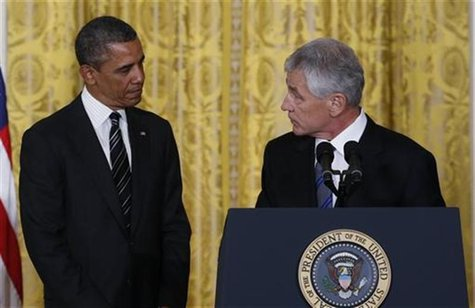 Former U.S. Senator Chuck Hagel (R) takes the podium after U.S. President Barack Obama (L) announced the nomination of Hagel to be his new S