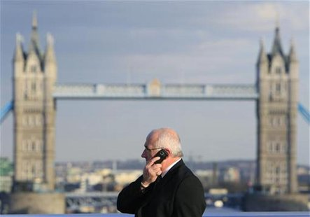 A man talks on a mobile telephone in front of Tower Bridge whilst walking across London Bridge in London March 1, 2010. REUTERS/Luke MacGreg