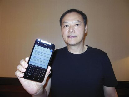 Peter Chou holds one of his devices sporting a new Myanmar font ahead of Monday's launch of the product in Yangon January 13, 2013. REUTERS/
