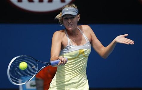 Maria Sharapova of Russia hits a return to compatriot Olga Puchkova during their women's singles match at the Australian Open tennis tournam