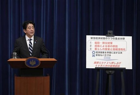 Japan's Prime Minister Shinzo Abe speaks next to a placard showing the government's emergency economic stimulus plan during a news conferenc
