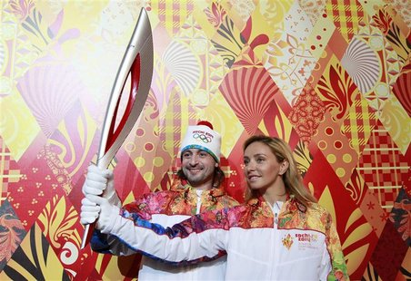Russian ice dancers Tatyana Navka (R) and Ilya Averbukh hold the Olympic torch for the Sochi 2014 Winter Olympics during a presentation cere
