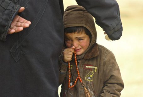A boy, standing next to his father, cries as they wait to receive humanitarian aid in the countryside of Idlib January 13, 2013. Picture tak