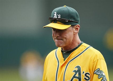 Oakland Athletics manager Bob Melvin returns to the dugout out after taking pitcher A.J. Griffin out of the game for tightness in his right