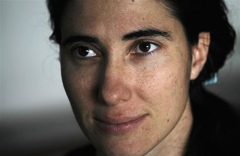 Cuban dissident blogger Yoani Sanchez listens to a question during an interview with Reuters at her home in Havana, in this February 9, 2011