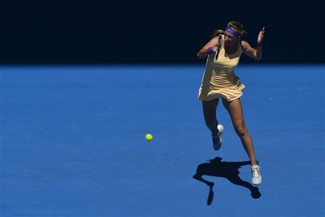 Victoria Azarenka of Belarus hits a return to Monica Niculescu of Romania during their women's singles match at the Australian Open tennis t