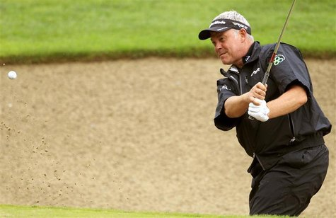 Darren Clarke of Northern Ireland hits out of the bunker onto the 9th green during the first round of the European Masters golf tournament i