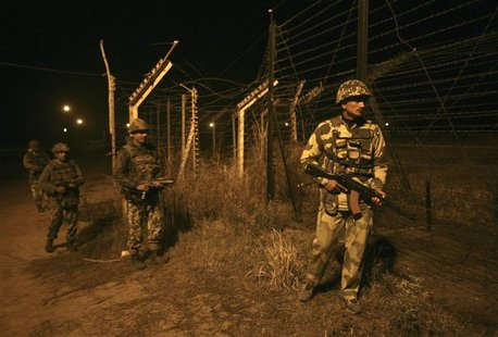 Indian Border Security Force (BSF) soldiers walk during night patrol near the fenced border with Pakistan in Abdullian, southwest of Jammu J