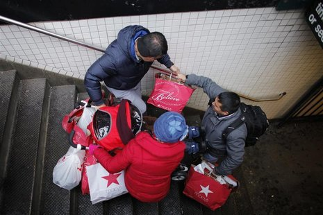 Shoppers go down the stairs with some bags and a stroller after their making purchases in New York, December 26, 2012. The 2012 holiday seas