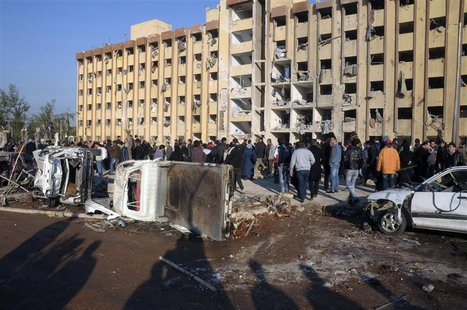 Syrian security personnel and civilians gather at the site where two explosions rocked the University of Aleppo in Syria's second largest ci