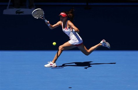 Agnieszka Radwanska of Poland hits a return to Irina-Camelia Begu of Romania during their women's singles match at the Australian Open tenni