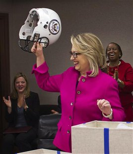 U.S. Secretary of State Hillary Clinton holds up a football helmet with the State Department logo on it, presented to her during a weekly me