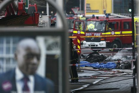 Smoke rises from debris as police and emergency services attend the scene of a helicopter crash in Vauxhall, south London January 16, 2013.