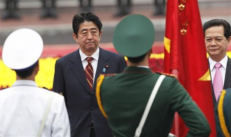 Japan's Prime Minister Shinzo Abe (L) and his Vietnamese counterpart Nguyen Tan Dung review the guard of honour during a welcoming ceremony