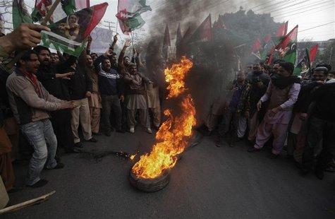 Supporters of Pakistan People's Party (PPP) hold party flags as they burn tyres during a protest against the Supreme Court decision to arres