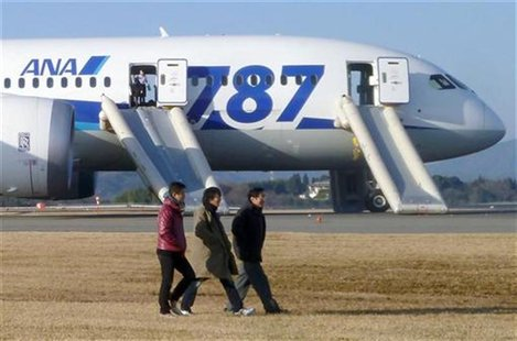 Passengers walk away from All Nippon Airways' (ANA) Boeing Co's 787 Dreamliner plane which made an emergency landing at Takamatsu airport, w