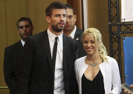 Colombian pop star and the United Nations Children's Fund (UNICEF) ambassador, Shakira, walks with her boyfriend, Barcelona soccer player Ge