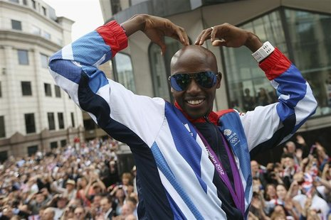 "Long distance runner Mo Farah makes his trademark ""Mobot"" pose during a parade of British Olympic and Paralympic athletes through London Sep"