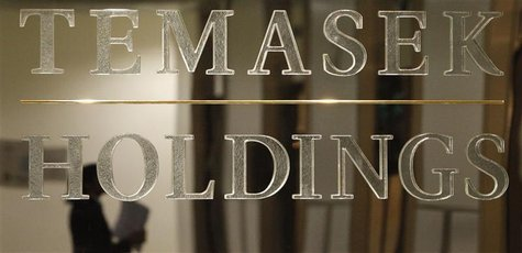 A staff member is reflected in a Temasek Holdings logo at their headquarters before the presentation of Temasek's annual review in Singapore