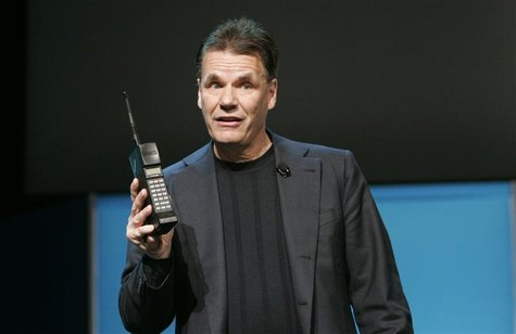 Former Nokia President and Chief Executive Olli-Pekka Kallasvuo holds a Nokia mobile phone from 1987 during his keynote speech at the 2010 I