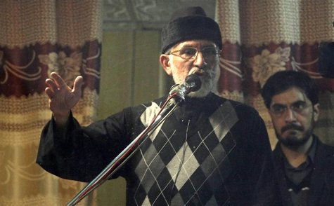 Sufi cleric and leader of the Minhaj-ul-Quran religious organisation Muhammad Tahirul Qadri (L) addresses his supporters from behind the win