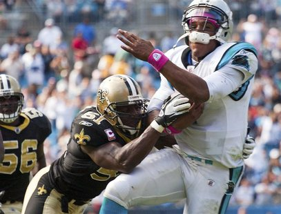 Carolina Panthers' quarterback Cam Newton (R) is hit by New Orleans Saints' middle linebacker Jonathan Vilma during an NFL football game in