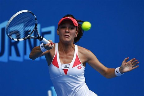 Agnieszka Radwanska of Poland hits a return to Heather Watson of Britain during their women's singles match at the Australian Open tennis to