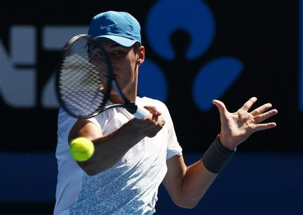 Bernard Tomic of Australia hits a return to Daniel Brands of Germany during their men's singles match at the Australian Open tennis tourname