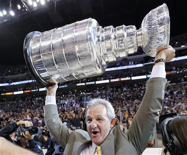 Los Angeles Kings head coach Darryl Sutter hoists the Stanley Cup after the Kings defeated the New Jersey Devils in Game 6 of the NHL Stanle