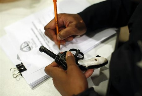 An Evanston police officer documents some information on a firearm that was turned in as part of an amnesty-based gun buyback program in Eva