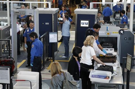A man is screened with a backscatter x-ray machine as travellers go through a TSA security checkpoint in terminal 4 at LAX, Los Angeles Inte