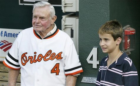 Former Baltimore Orioles manager and member of Major League Baseball's Hall of Fame, Earl Weaver stands with his grand son Jake in the dugou