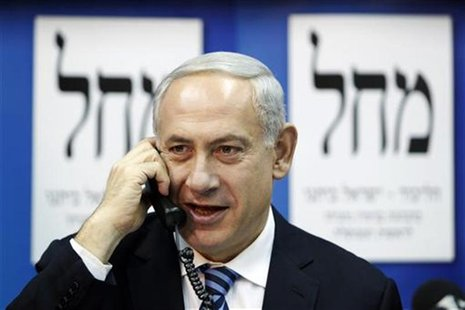 Israel's Prime Minister Benjamin Netanyahu (C) speaks on the phone to persuade citizens to vote for his party at the Likud-Yisrael Beitenu h