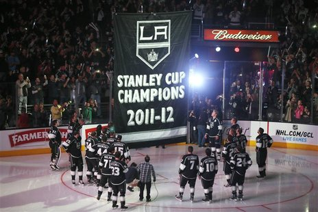 Los Angeles Kings players watch as their Stanley Cup championship banner is raised at the Staples Center before their NHL hockey game agains