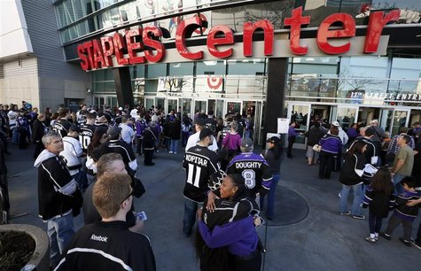 A Staples Center employee hugs a Los Angeles Kings fan as fans return for the first NHL game of the Kings' season against the Chicago Blackh