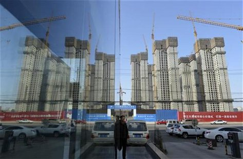 A construction site of a residential compound is reflected on the glass facades of a office building in Taiyuan, Shanxi province, January 15