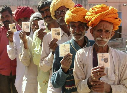 Villagers pose with their identity cards as they stand in line to open a bank account at a camp organised by a private bank in a village at