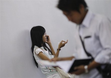 A girl talks on a mobile phone in a training school in Yangon January 19, 2013. REUTERS/Soe Zeya Tun