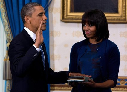 U.S. President Barack Obama takes the oath of office as frst lady Michelle Obama holds a bible during the official swearing-in ceremony at t
