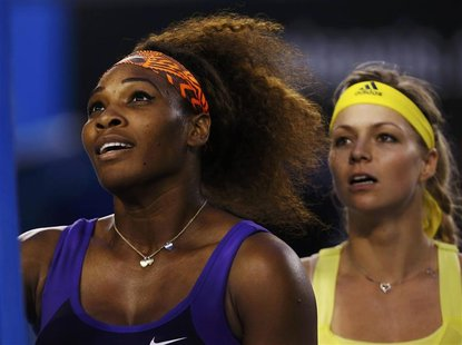 Serena Williams of the U.S. and Maria Kirilenko of Russia (R) shake hands with the chair umpire after their women's singles match at the Aus