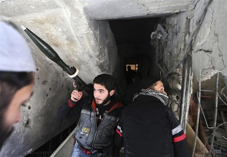 Fighters from Fateh al Sham unit of the Free Syrian Army enter a house in Haresta neighbourhood of Damascus January 20, 2013. REUTERS/Goran