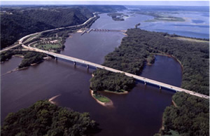 View looking north as Interstate 90 crosses from La Crosse Wisconsin to Dresbach Minnesota on the left.  Also visible, US Highway 61 interchange with I-90 on left and the Army Corps of Engineers Dresbach Lock and Dam on the Mississippi River's main channel.  Photo courtesy MN DOT.