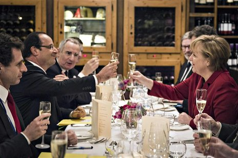 German Chancellor Angela Merkel (R) and French President Francois Hollande salute to each other during a private dinner in a Berlin restaura
